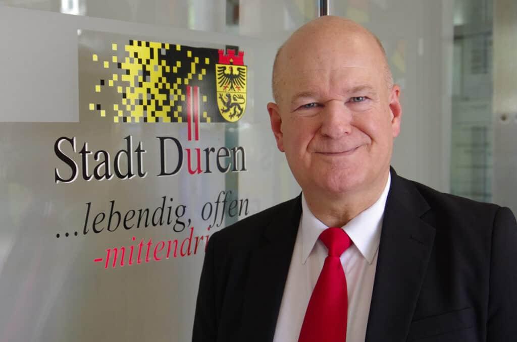 Frank Peter Ullrich nebem dem Logo der Stadt düren